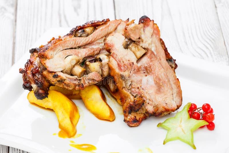 烤猪肉充塞用蘑菇、桃子、阳桃、蔓越桔和甜调味汁在板材在木背景 库存图片