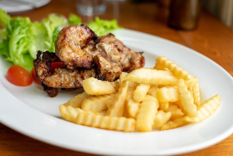 烤猪肉和薯条,安排在与沙拉菜的一个美丽的白色食物盘,看吃西部主菜 免版税库存图片