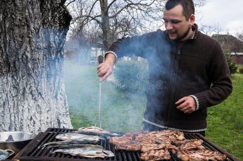 烤猪肉和鱼的年轻人 免版税图库摄影