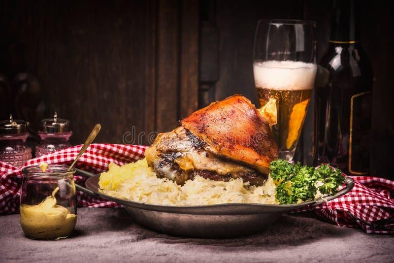 烤猪肉指关节eisbein用土豆泥,被炖的泡菜、啤酒和芥末在土气厨房用桌上在黑暗求爱 免版税库存图片