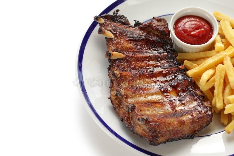 烤猪肉排骨和炸薯条 库存照片