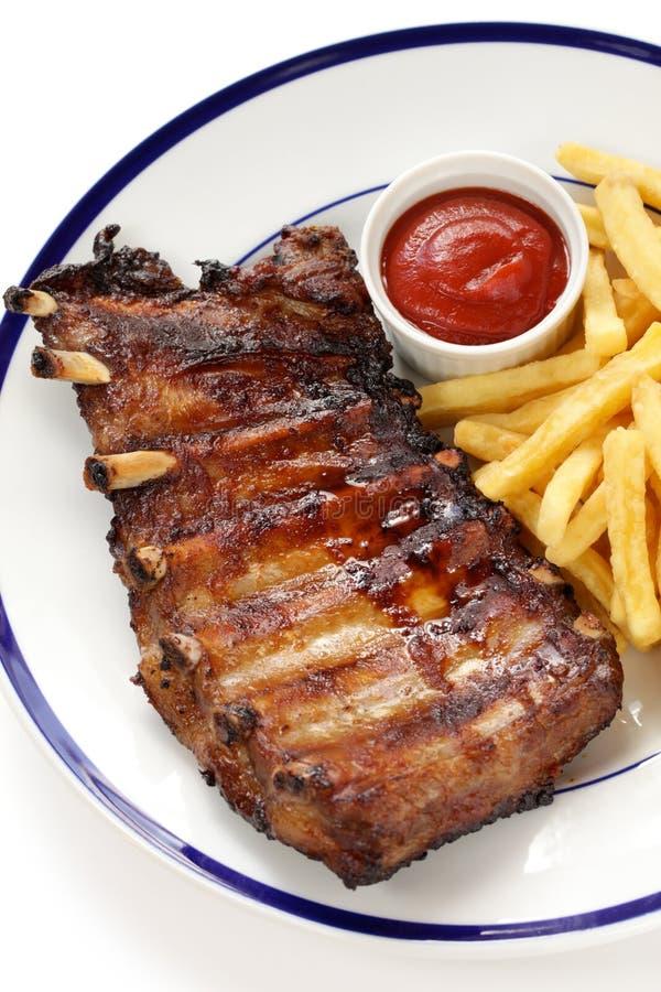烤猪肉排骨和炸薯条 免版税库存照片