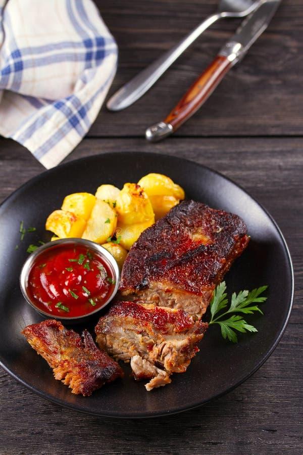 烤猪肉排骨用在黑色的盘子的油炸物 Roasted切了烤肉肋骨 免版税库存图片