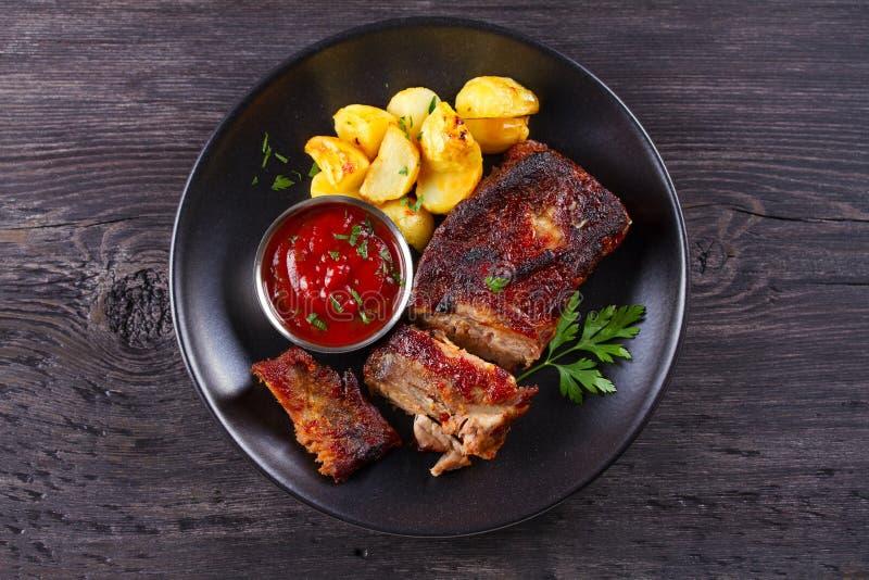 烤猪肉排骨用在黑色的盘子的油炸物 Roasted切了烤肉肋骨 库存照片
