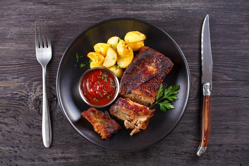 烤猪肉排骨用在黑色的盘子的油炸物 Roasted切了烤肉肋骨 图库摄影