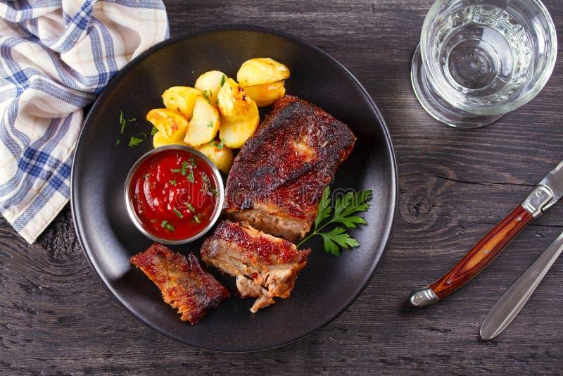 烤猪肉排骨用在黑色的盘子的油炸物 Roasted切了烤肉肋骨 免版税库存照片