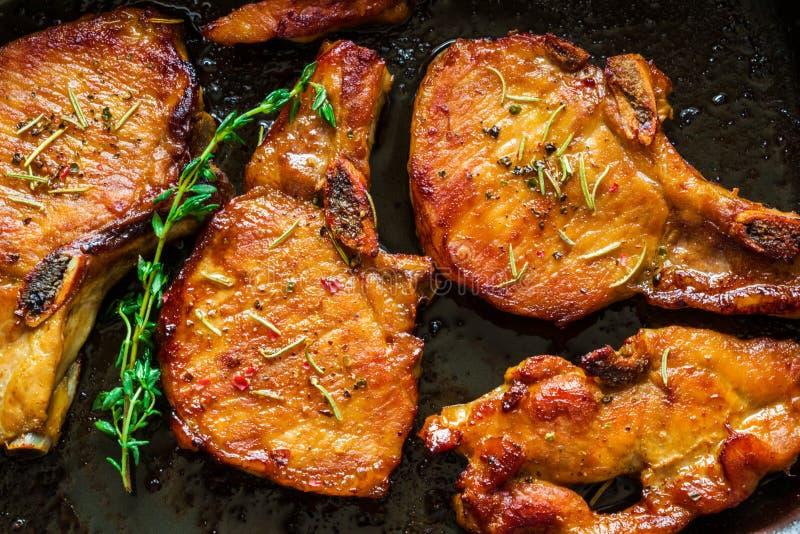 烤猪肉牛排、炸肉排与骨头和麝香草在黑烤板,顶视图 免版税库存照片