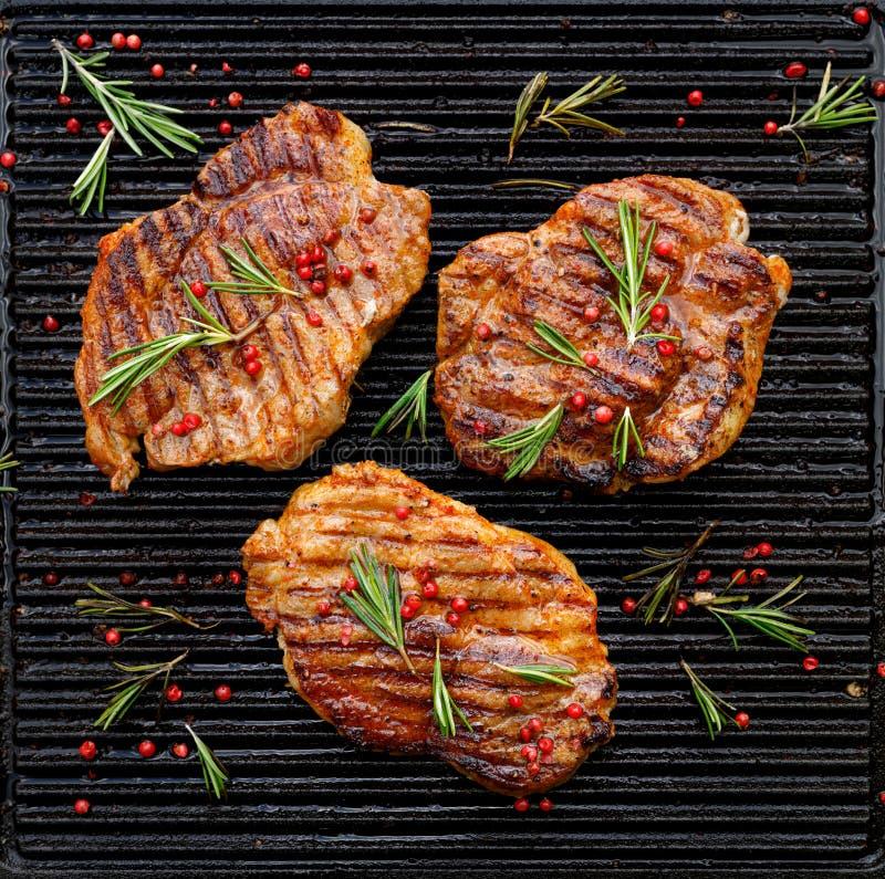 烤猪肉牛排、猪肉脖子增加草本和香料在格栅板材,顶视图 库存照片