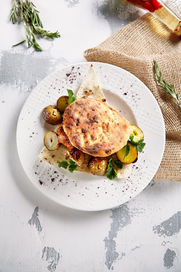 烤猪肉用土豆、香料和皮塔饼面包 库存照片