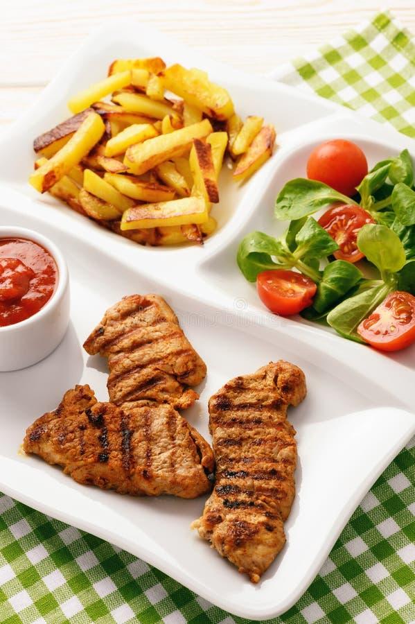 烤猪里脊肉、沙拉和油煎的土豆在白色板材 库存照片