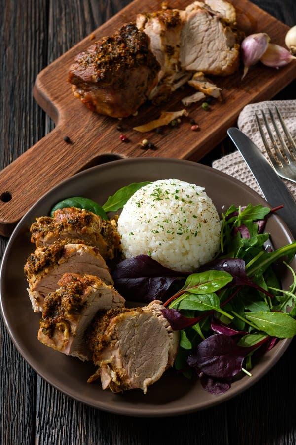 烤猪里脊肉服务用沙拉的煮沸的米和混合 库存图片