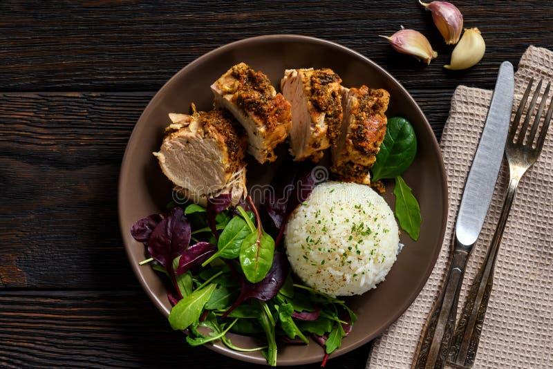 烤猪里脊肉服务用沙拉的煮沸的米和混合 库存照片