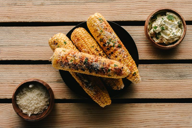 烤玉米顶视图在香料和黄油之间的用在木的荷兰芹 免版税库存照片