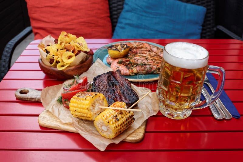烤玉米,与杯子的热的bbq肋骨储藏啤酒 免版税库存图片