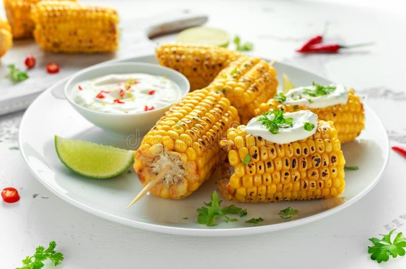 烤甜玉米用白色墨西哥调味汁、辣椒和石灰 健康夏天食物 库存照片