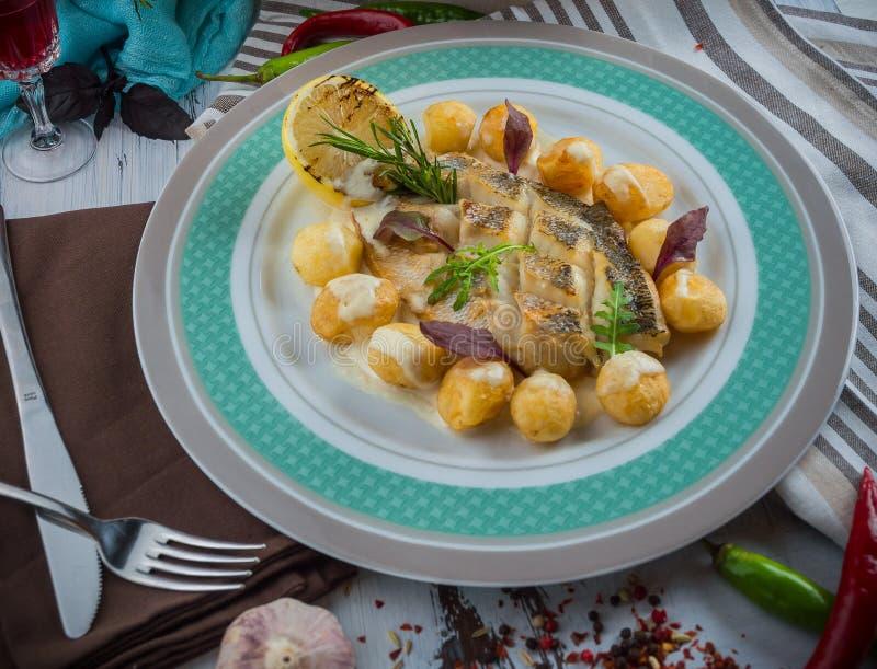 烤白色鱼用土豆 库存图片