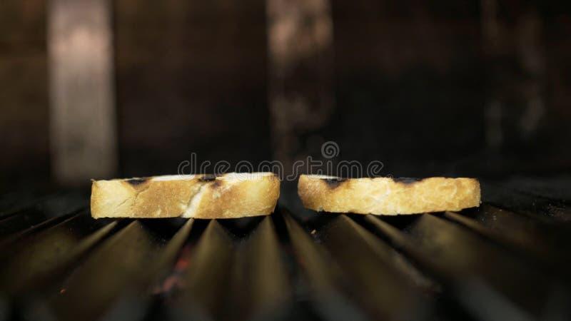 烤的两片面包片特写镜头  r 在格栅的烤箱油煎的芬芳简单的面包切片 在格栅的多士 免版税库存图片