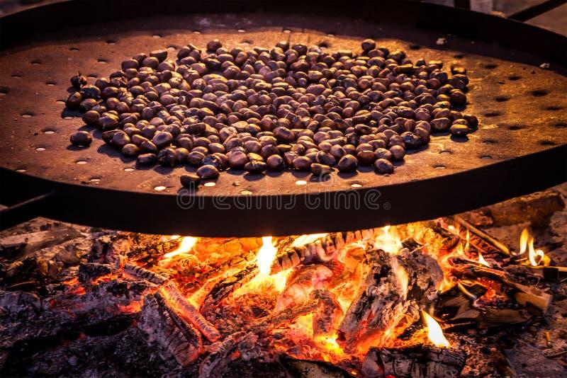 烤的栗子 在火炉燃烧的大平底锅 库存图片