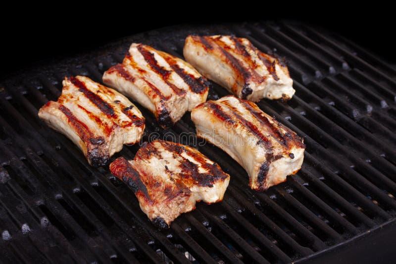 烤稠粘的肋骨和炸猪排在格栅 库存图片