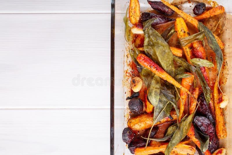 烤箱烘烤了红萝卜和甜菜根与贤哲叶子和大蒜 免版税库存图片