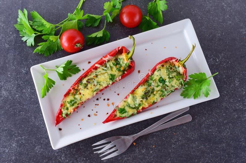 烤箱煮熟的红色辣椒粉充塞用乳酪、大蒜和草本在一块白色板材有parcley的和的西红柿 库存图片