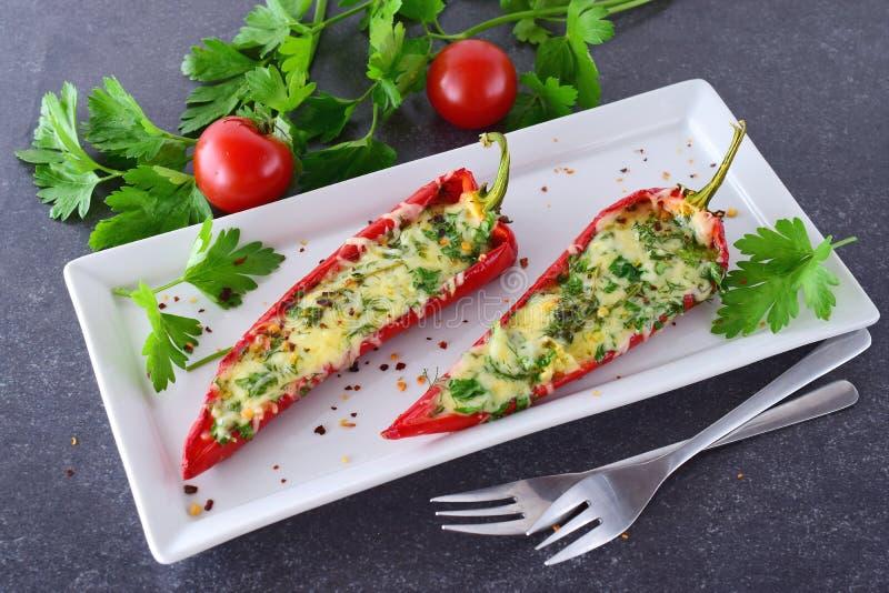 烤箱煮熟的红色辣椒粉充塞用乳酪、大蒜和草本在一块白色板材有parcley的和的西红柿 免版税图库摄影