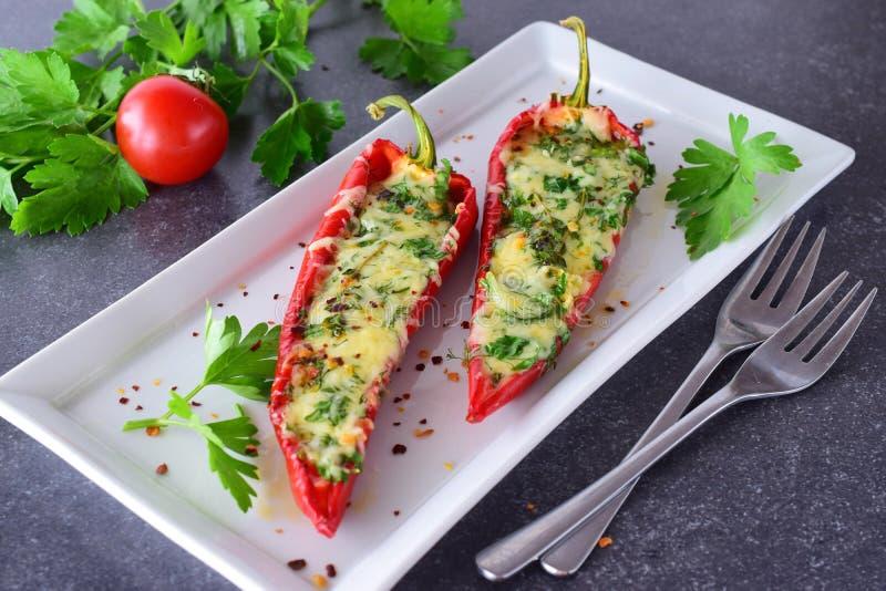 烤箱煮熟的红色辣椒粉充塞用乳酪、大蒜和草本在一块白色板材有parcley的和的西红柿 库存照片