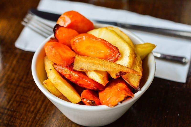 烤红萝卜和欧洲防风草在碗被安置在餐馆表 免版税图库摄影