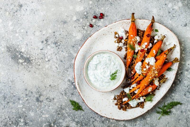 烤红萝卜扁豆沙拉用希脂乳、草本酸奶和dukkah在轻混凝土背景 素食食物 免版税库存图片