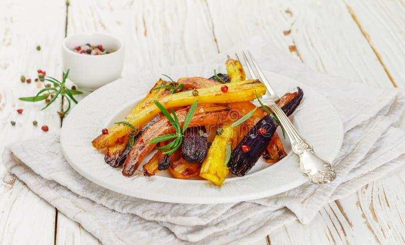 烤红萝卜用迷迭香、粗糙的海盐和胡椒 库存图片