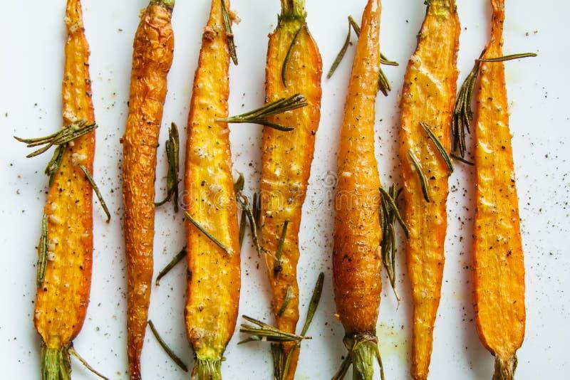 烤红萝卜用迷迭香和香料在一张白色桌上 图库摄影