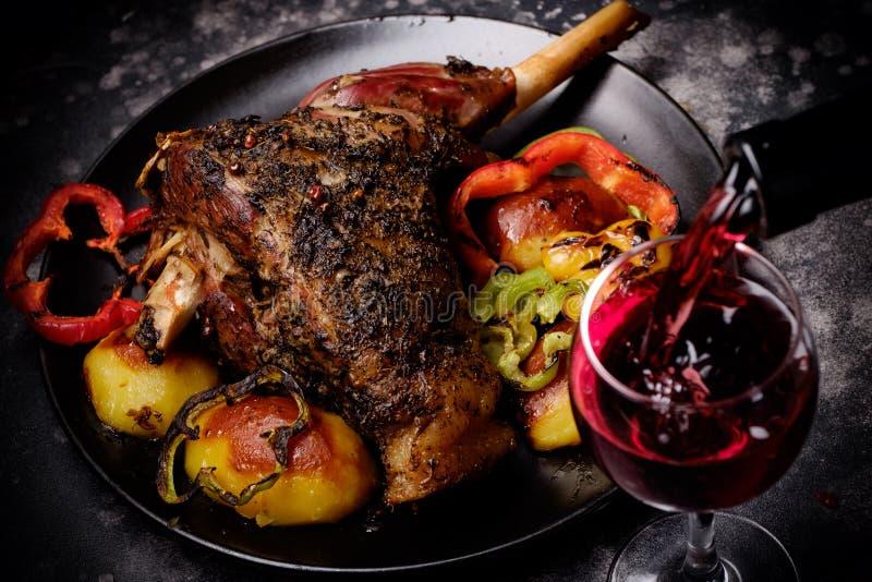 烤羊羔小腿用香料和烤菜和红葡萄酒玻璃倾吐了用酒 免版税库存照片