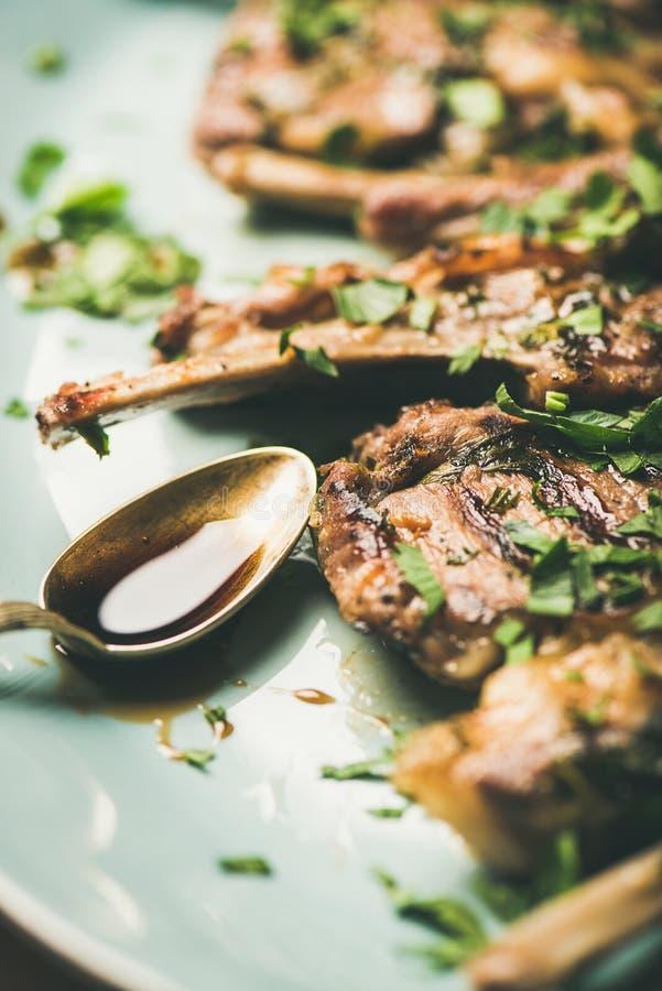 烤羊羔肋骨用绿色荷兰芹和调味汁,特写镜头 图库摄影