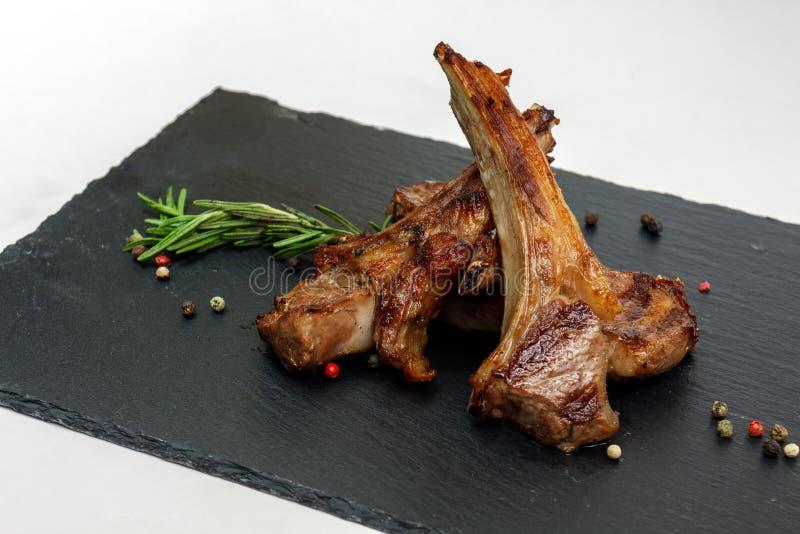 烤羊羔肋骨用迷迭香和胡椒在黑色的盘子 免版税库存图片