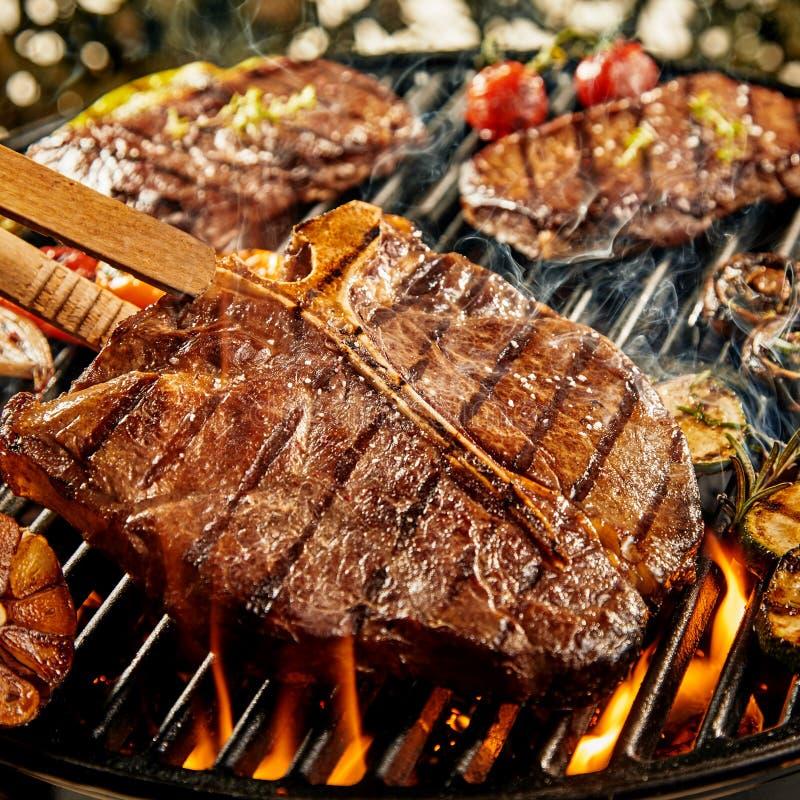 烤肉在火的鲜美用卤汁泡的丁骨牛排 免版税库存图片