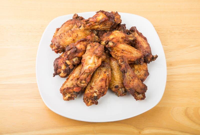烤肉在白色板材的鸡翼 库存图片