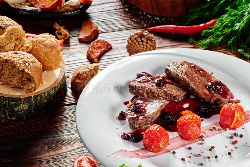 烤肉大奖章和红色调味汁在一块白色板材在黑暗的木背景 库存图片