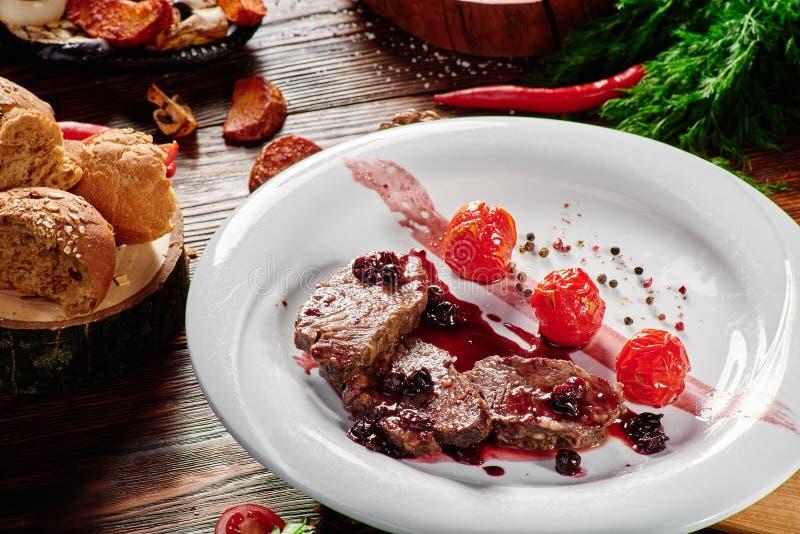 烤肉大奖章和红色调味汁在一块白色板材在黑暗的木背景 免版税库存图片