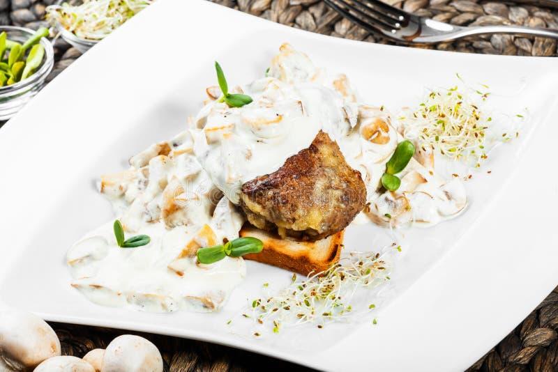 烤肉牛排小牛肉大奖章用乳酪调味料用在板材的蘑菇 图库摄影
