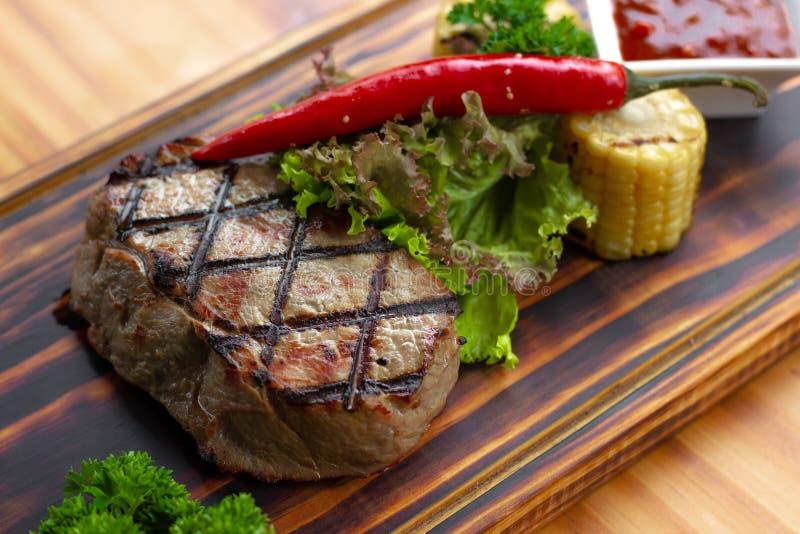 烤肉牛排用炽热胡椒、草本、玉米和西红柿酱在木板 烤牛排关闭  食物 库存图片