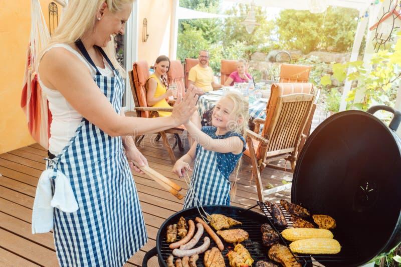 烤肉聚会在有妈妈和她的女儿的庭院里格栅的 免版税库存图片