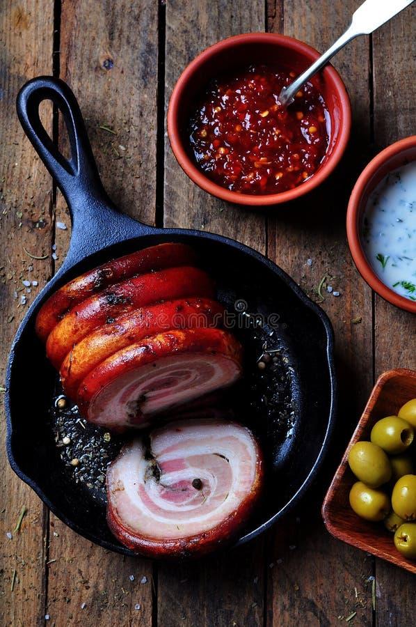 烤肉腹部卷用胡椒,海盐,烘干了迷迭香、蓬蒿和大蒜在一张木桌上 土气样式 免版税库存图片