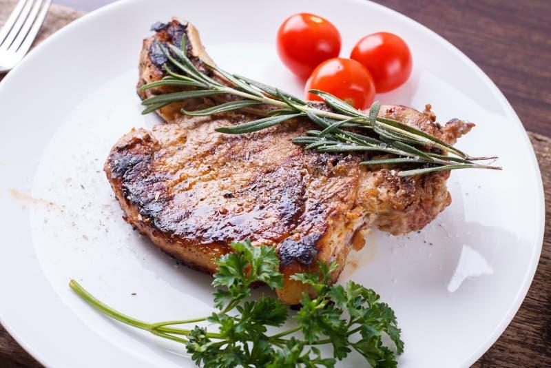 烤肋骨牛排用在白色盘的迷迭香 图库摄影