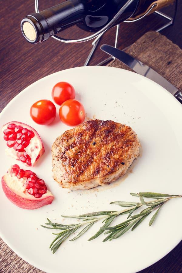 烤肋骨牛排用在白色盘的迷迭香 免版税图库摄影
