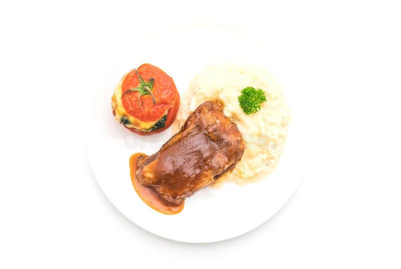 烤肋骨猪肉用土豆泥和菠菜在蕃茄烘烤了 免版税图库摄影