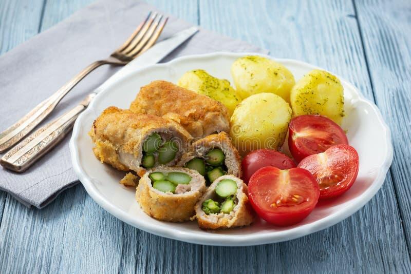 烤芦笋充塞了猪里脊肉供食用土豆和蕃茄 免版税库存图片
