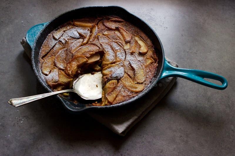 烤苹果clafoutis (法国乳蛋糕蛋糕)在生铁平底锅 库存照片