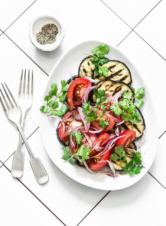 烤茄子和蕃茄,红洋葱,橄榄油沙拉-可口素食快餐,开胃菜,在轻的背景的塔帕纤维布,顶面 库存照片
