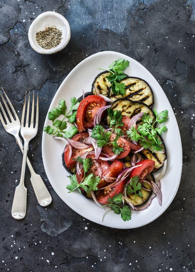烤茄子和蕃茄,红洋葱,橄榄油沙拉-可口素食快餐,开胃菜,在黑暗的背景的塔帕纤维布,顶面 库存照片