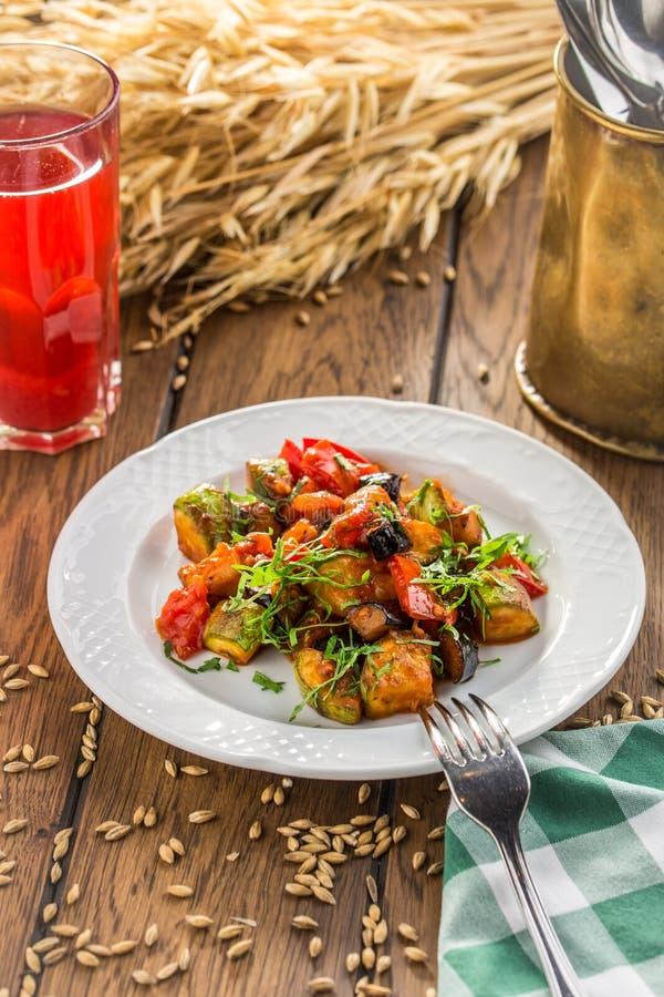 烤菜温暖沙拉用夏南瓜、茄子、葱、胡椒和蕃茄用莓果汁在木桌上 库存图片